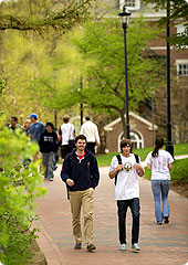 Students walking a path on the campus green between classes.