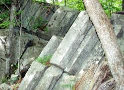 The formation is found part way up the Bald Knob Connector Trail off the Shannon Brook Carriage Road, found in the Lake Region Conservation Trust's Castle in the Clouds network in the Ossipee Range.