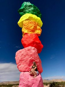Girl in front of rainbow painted rocks