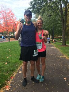 Man and woman post run holding medals