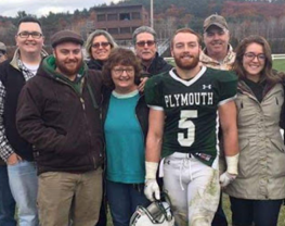 Football player standing with family