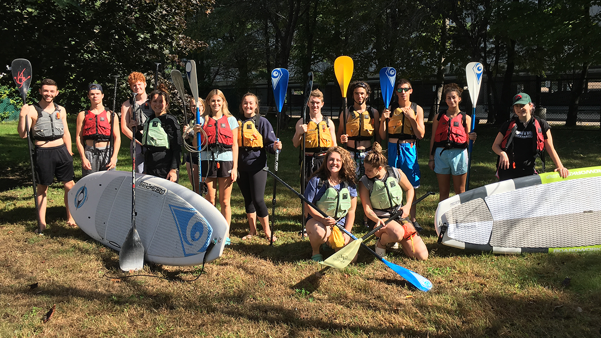Paddleboard composition class standing with paddles and boards for photo.