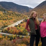 Two women pose in front of scenic road.