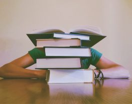 Stressed woman behind stack of books.
