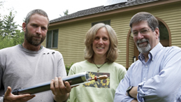 "Chris, Sandra and Peter display the ""evacuated tube"" made by Apricus, that comprises the panel. The vacuum created between the glass walls is the insulation that allows these tubes to function better than traditional flat panels in climates like N.H. The copper piece sticking out from the end of the tube in this photo is the heat pipe that transfers the captured heat into the manifold on the roof."
