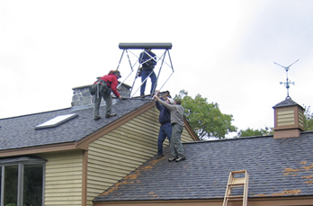 "An ""energy raiser"" in action. PAREI members pitch in to install a solar water heating system."