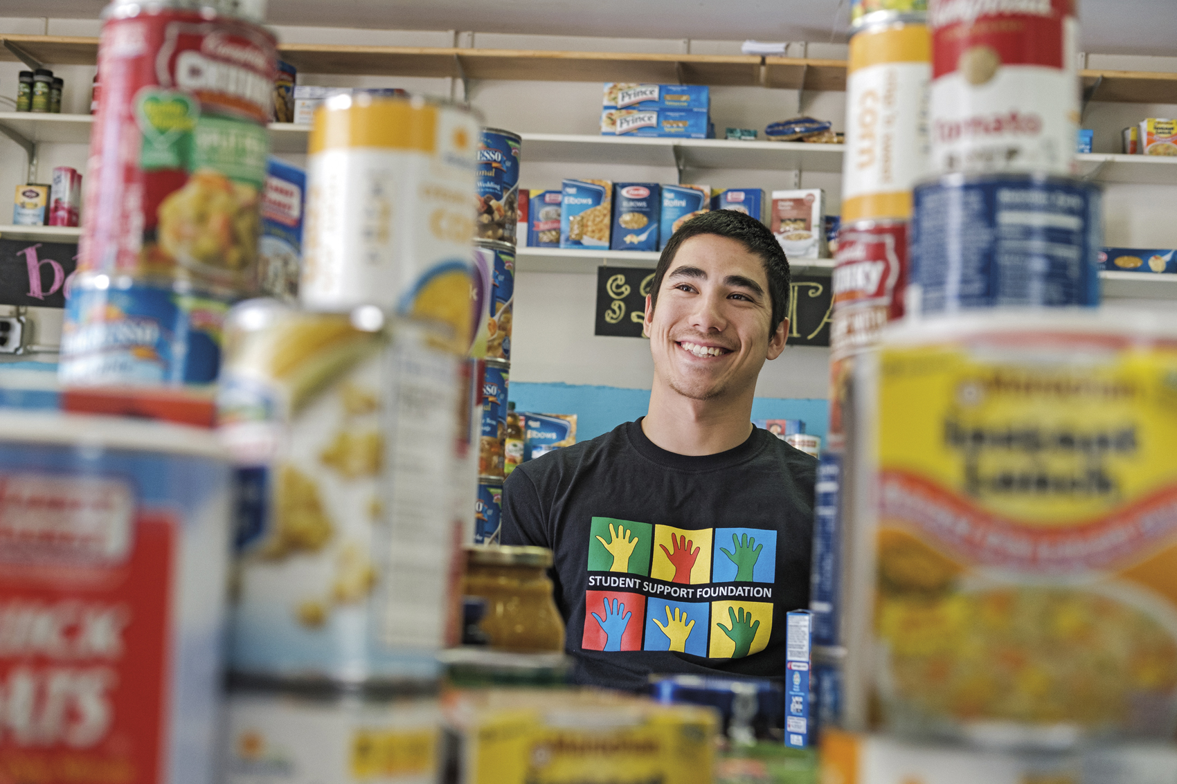 Adam Murata '16 volunteers at the Student Support Foundation food pantry, where 66 students in need were served last year. The food pantry also delivered eight large crates of food to the financial aid office to be distributed to still more students. Kaleb Hart '11 photo.